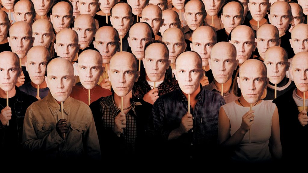 A bunch of people holding up John Malkovich masks